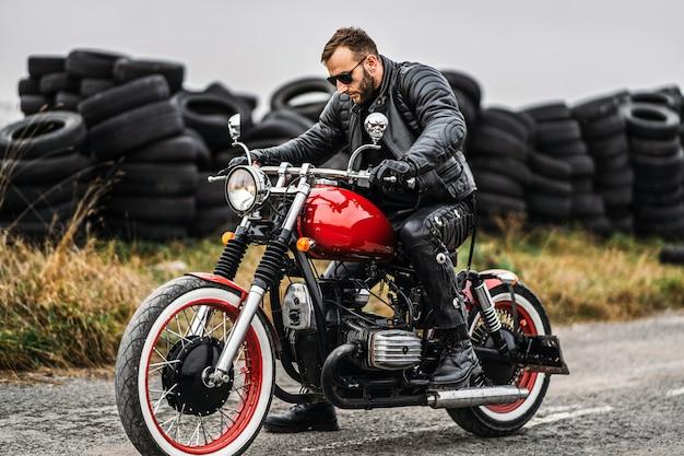 ライダーと赤いバイク。黒革のジャケットとズボンの男は、オートバイを開始します。 Premium写真