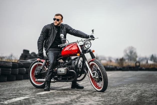 Красный мотоцикл с наездником. человек в черной кожаной куртке и брюках стоит боком посреди дороги. Premium Фотографии