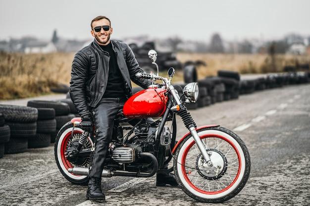 ライダーと赤いバイク。黒い革のジャケットとズボンの男は、道路の真ん中に横に立っています。 Premium写真
