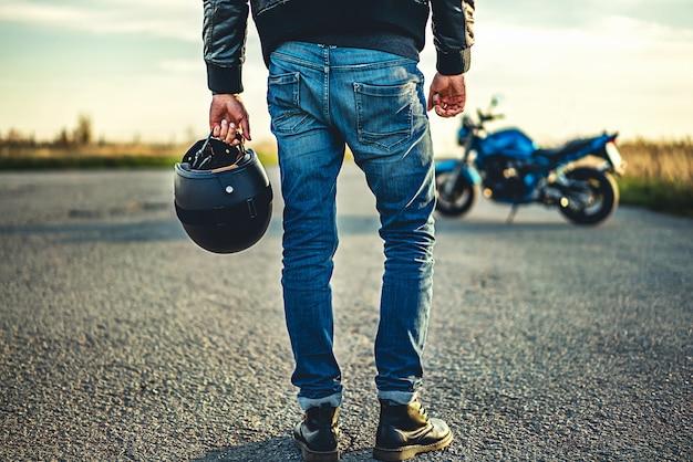 Человек на спортивном мотоцикле, открытый на дороге Premium Фотографии