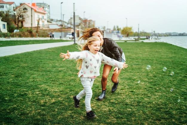 彼女の小さな娘を持つ母は公園で楽しんでいます Premium写真