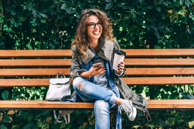 巻き毛を持つ少女はコーヒーを飲み、スマートフォンを屋外で使う Premium写真