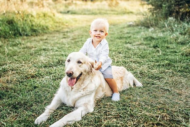 Симпатичный маленький мальчик веселиться с собакой Premium Фотографии