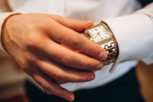 彼の手に時計を見て Premium写真