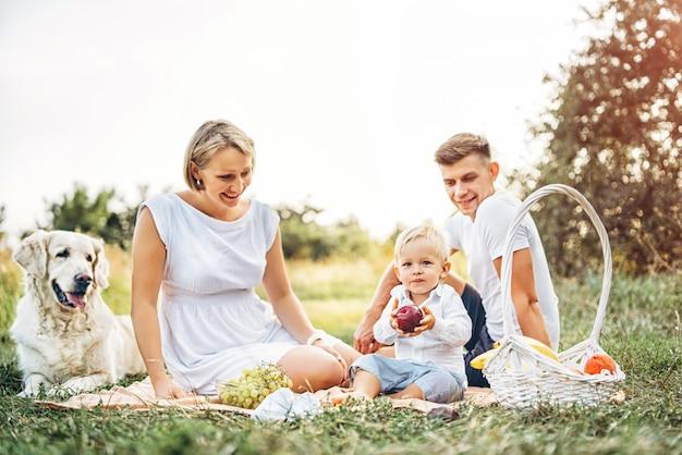 犬と一緒にピクニックに若いかわいい家族 Premium写真