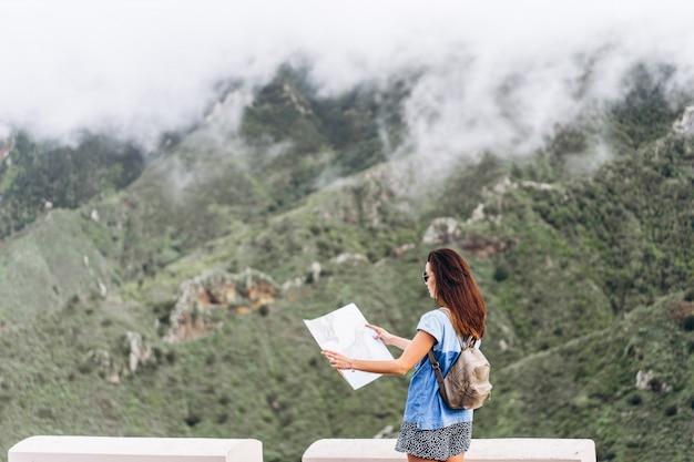 地図と山の中の屋外のサングラスでかなりブルネットの少女。 Premium写真