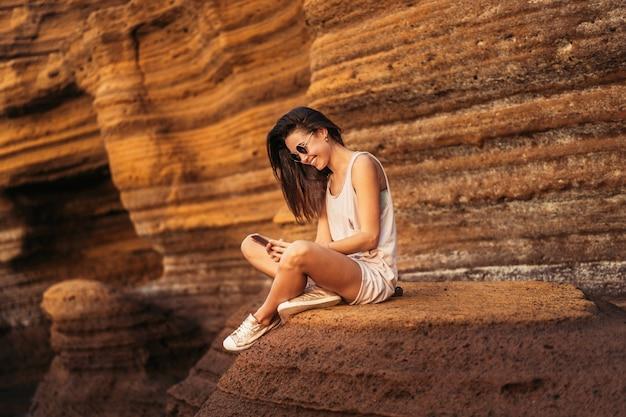 Девушка брюнет довольно длинных волос туристская ослабляя на камнях около моря. Premium Фотографии