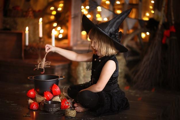 Маленькая ведьма хеллоуин читает заклинание над горшком детство хэллоуин, Premium Фотографии