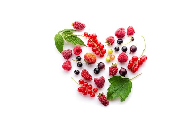 Сердце из разных свежих ягод как символ любви к здоровой сырой веганской пище Premium Фотографии