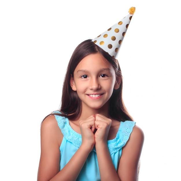 休日のお祝いを待っているお祝い帽子で幸せな笑顔の女の子 Premium写真