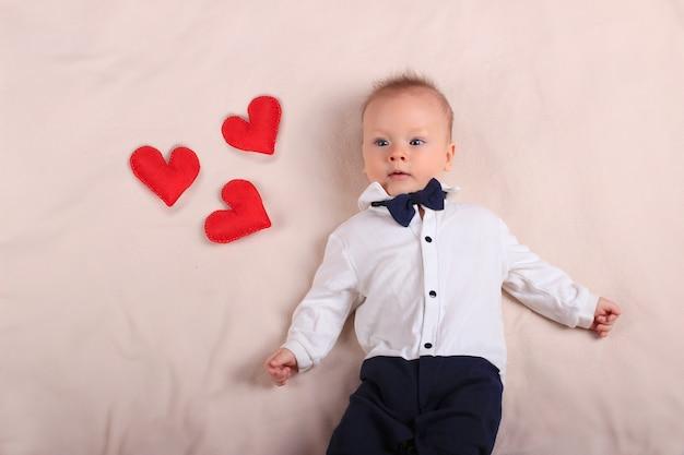 母の日とコピースペースと愛の象徴として赤いおもちゃの心とタキシードと蝶ネクタイを着てかわいい男の子 Premium写真