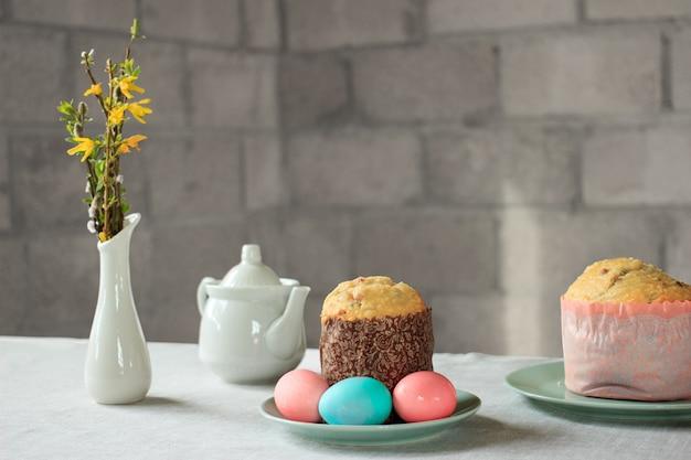 パステルピンクとブルーのイースターエッグ、ロシアと正統派のイースターパンクリーチまたはパスカ、春レンギョウの花とテーブルの上の柳の尾状花序と花瓶 Premium写真