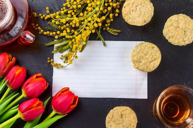 チューリップ、ミモザ、紅茶とカップケーキブラックストーンボードの背景に春のグリーティングカード。 Premium写真