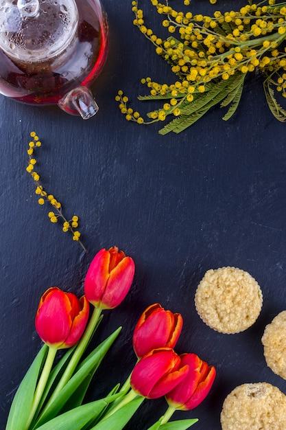 チューリップ、ミモザ、紅茶と黒の石のボードの背景にカップケーキの女性の日グリーティングカード。 Premium写真