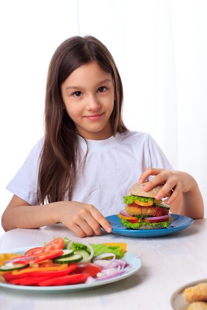 グリーンサラダ、全粒粉の小麦粉パンと分離されたひよこ豆のフリッターと健康的なビーガンベジタリアンバーガーを食べる少女 Premium写真