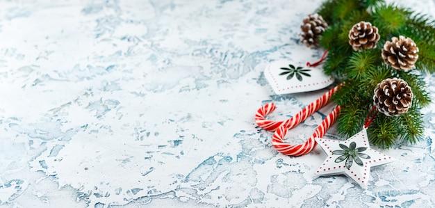 Рождественская композиция с еловой веткой, елочные украшения, леденцы Premium Фотографии