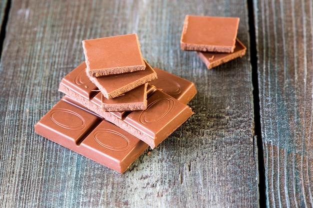木製の背景にチョコレートのかけら Premium写真