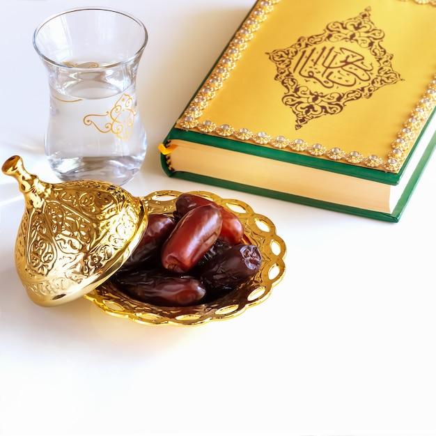 有機乾燥日程アラビアゴールデンプレート、カップ水とコーランの本。 Premium写真