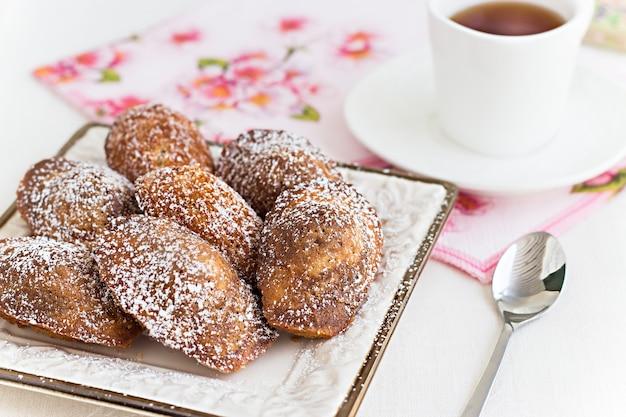 フレンチクッキーマドレーヌと紅茶の白いカップ。コンセプトロマンチックな朝食。 Premium写真