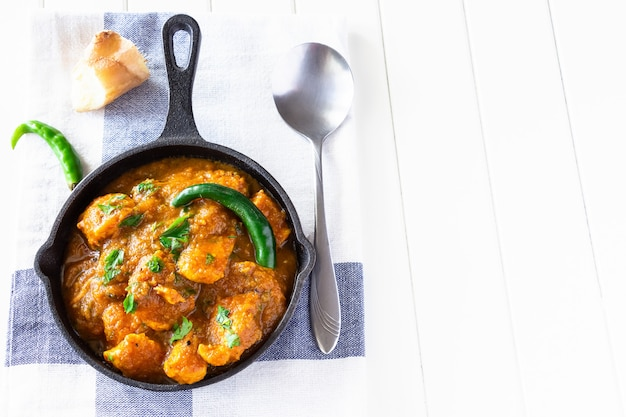伝統的なインドのバターチキンカレーをクローズアップし、レモンとチャパティのパンを添えてください。上面図。コピースペース Premium写真