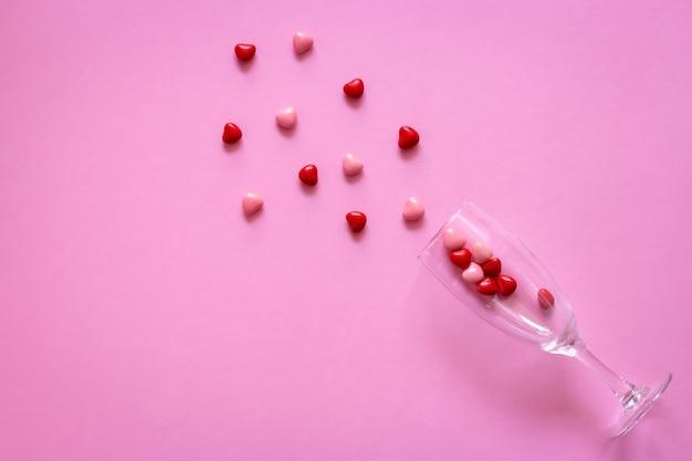 ワイングラスにハートのお菓子や丸薬の形。コンセプトバレンタインデーや薬、薬局。 Premium写真