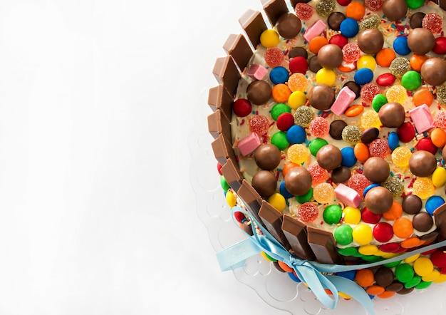 ピニャータケーキ。色とりどりのキャンディーぬいぐるみの中の誕生日ケーキ。 Premium写真