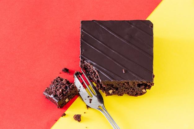 クルミとチョコレートビーガンブラウニーケーキツートンカラーの背景オレンジと黄色 Premium写真