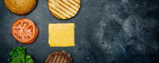自家製バーガーの組成(レシピ)。暗い背景の古典的なハンバーガーの製品。 Premium写真