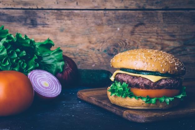 木製の背景に牛肉と自家製バーガー(チーズバーガー)。古典的な自家製バーガー。 Premium写真