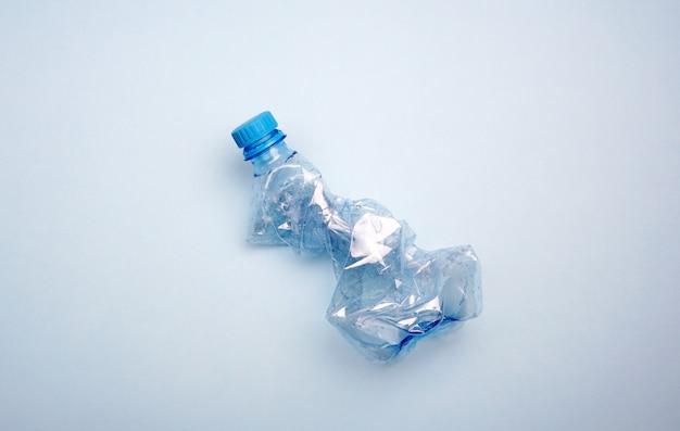 青の背景にペットボトル。海洋汚染の最小限の概念 Premium写真