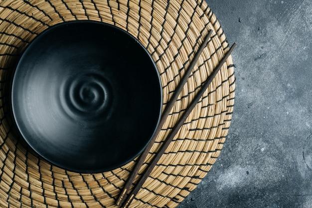 灰色の石に中国の箸で空の黒いボウル(手作りのセラミック) Premium写真