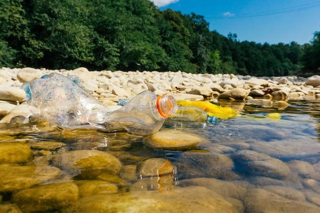 汚れたペットボトルとバッグ、水中のプラスチック Premium写真