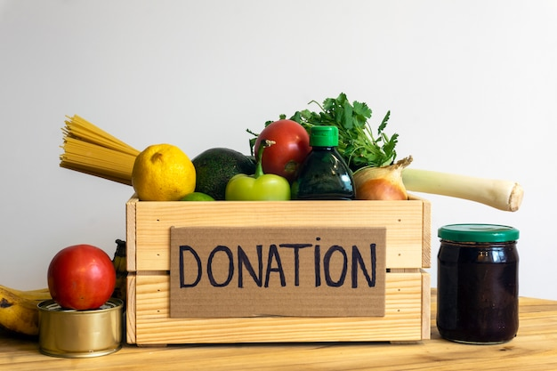 食品寄付のコンセプト。野菜、果物、その他の寄付用食品が入った募金箱 Premium写真