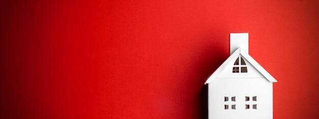 赤の背景に白の装飾的な家と最小限のクリスマスの背景。最小限のコンセプト。 Premium写真