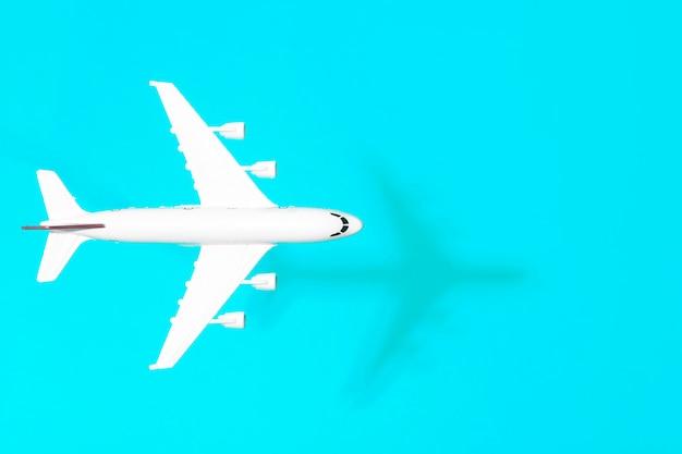 最小限の背景を旅行します。空の色付きの背景で飛行中の模型飛行機。コピースペース Premium写真
