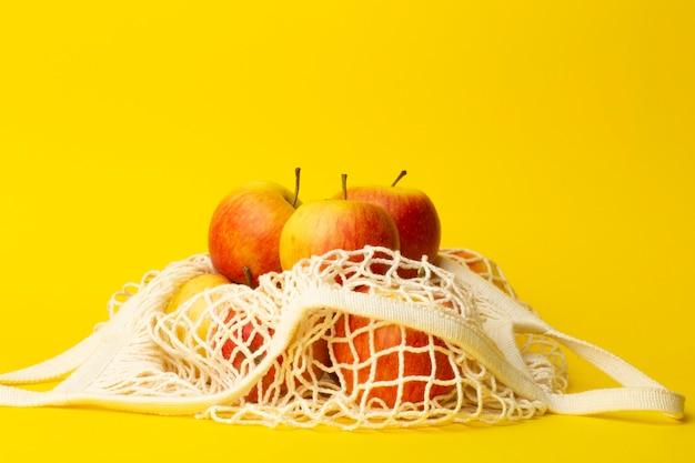 廃棄物ゼロのコンセプト。黄色の背景にひもの袋に入れたリンゴ。スーパーマーケットやショップのコンセプトにビニール袋はありません Premium写真