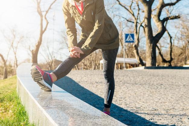 ジャケットとスニーカーの女性は午前中に公園でスポーツ演習を行います Premium写真