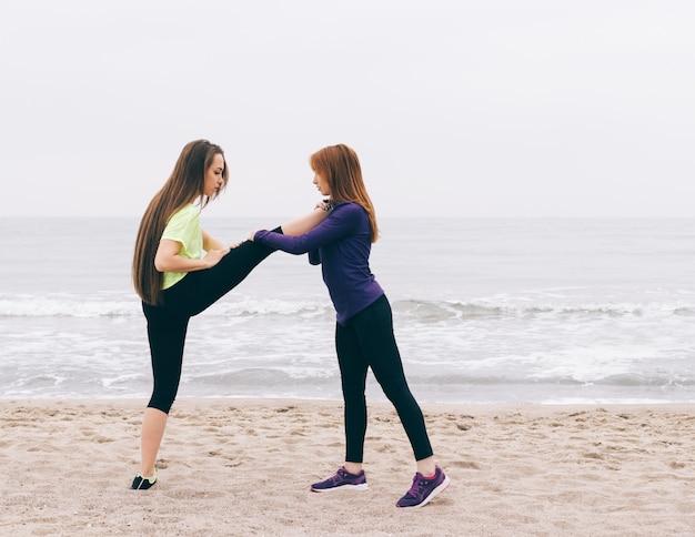 スポーツインストラクターは女の子がビーチでストレッチをするのを助けます Premium写真