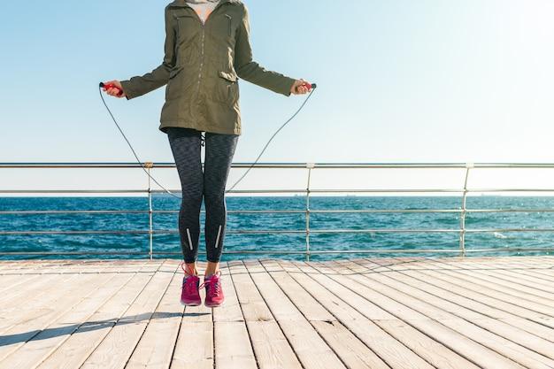 朝のジャケットとスニーカーでアスレチック女ジャンプ海の背景にロープ Premium写真