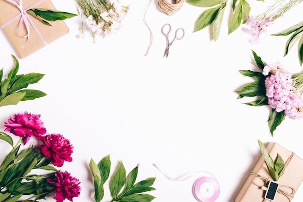 白い背景のお祝い組成:牡丹とカーネーション、ギフト、リボン、包装紙の花 Premium写真