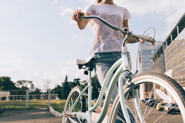 Обрезанное изображение молодой женщины в джинсах и футболке с велосипедом Premium Фотографии