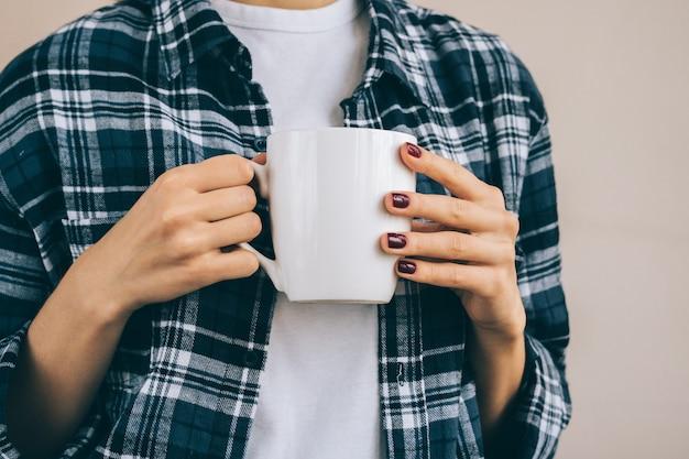ドリンクを飲みながら白いカップを保持している格子縞のシャツの女性の画像をトリミング Premium写真