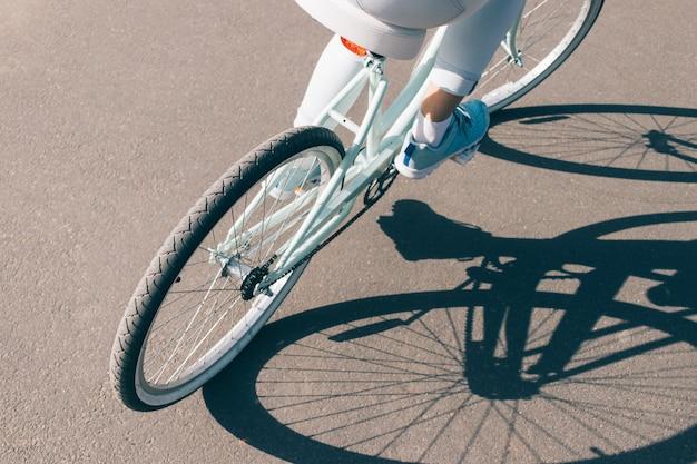 Вид со спины девушка едет на велосипеде по асфальту в солнечный день Premium Фотографии