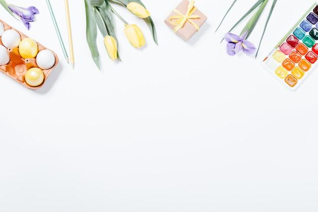 イースター組成の平面図:花、着色された卵、水彩絵の具 Premium写真