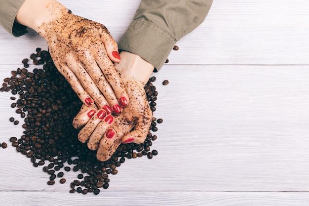 Крупный план женщины, применяющей скраб для кофе к ее рукам Premium Фотографии