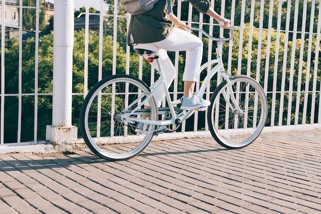 Крупным планом женщина в куртке и джинсах, езда на городском велосипеде Premium Фотографии