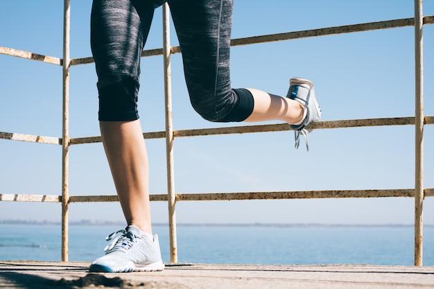 Спортивная молодая женщина, делающая упражнения для ног утром на море, крупный план Premium Фотографии