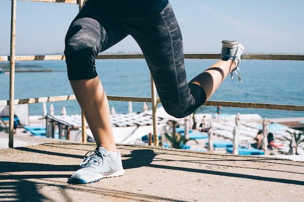 Стройная спортивная девушка делает приседания на пляже Premium Фотографии