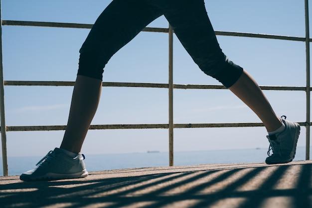 Красивые стройные ноги молодой спортивной женщины в синих кроссовках на фоне моря в утреннем свете крупным планом Premium Фотографии