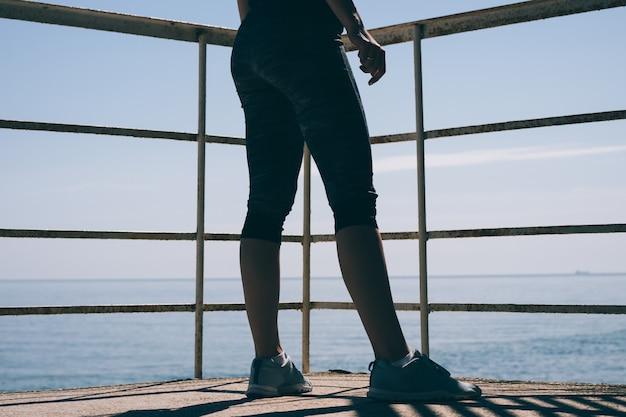 Стройные женские ножки в синих кроссовках и спортивные штаны на фоне моря ранним утром Premium Фотографии